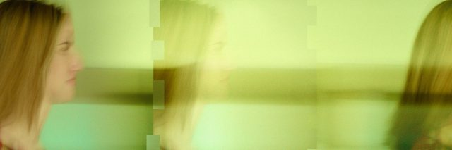 young woman, blurry image of walking through a room.
