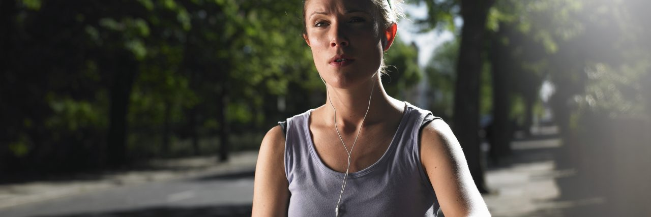Young woman jogging on street with mp3 player, checking time
