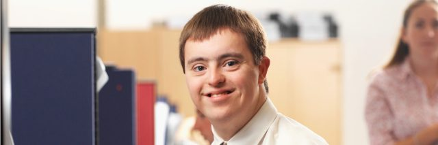 Young man with Down syndrome working in an office.