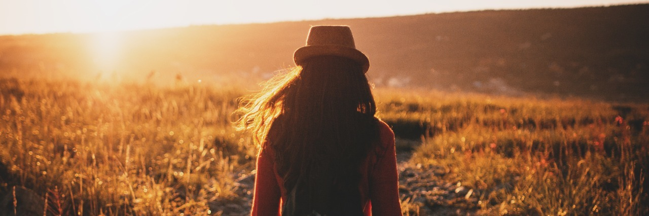 woman in a field at sunset facing away from camera