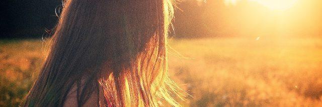 woman enjoying sunset in field long hair