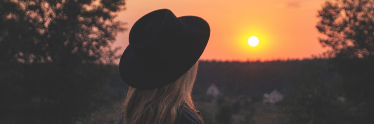 woman wearing hat watching sunrise