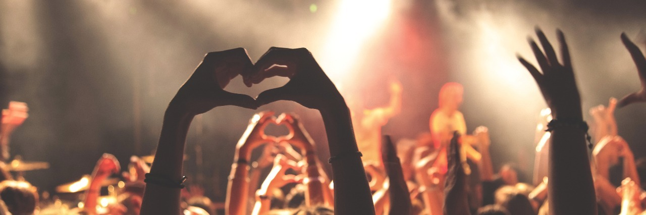 people celebrating at concert showing love sign