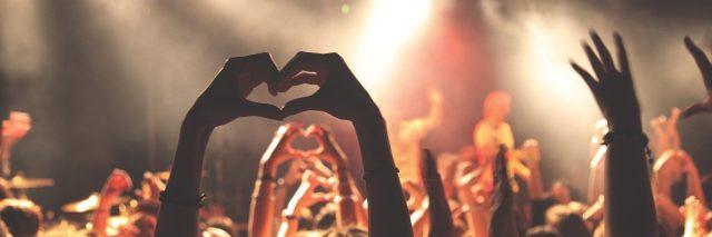 people celebrating at concert showing love sign
