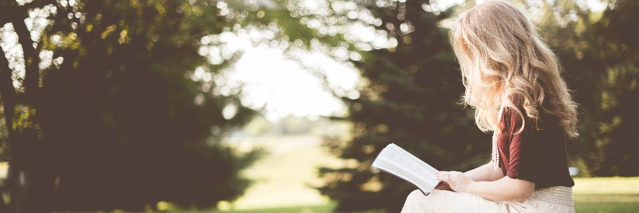woman in white skirt reading book in field