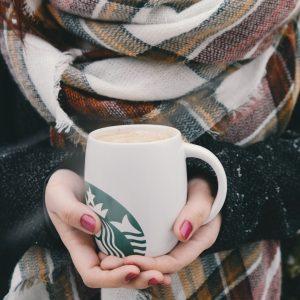woman with scarf holding starbucks coffee mug