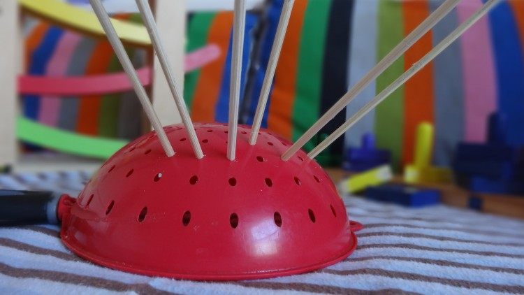 red colander with wooden skewers