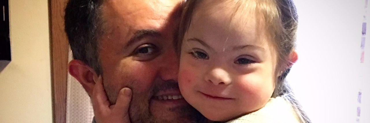 daughter with Down syndrome wearing white dress hugging dad'sface