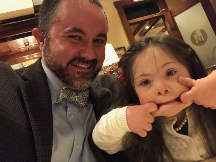 Dad posing with daughter with Down syndrome while she makes a silly face at the camera