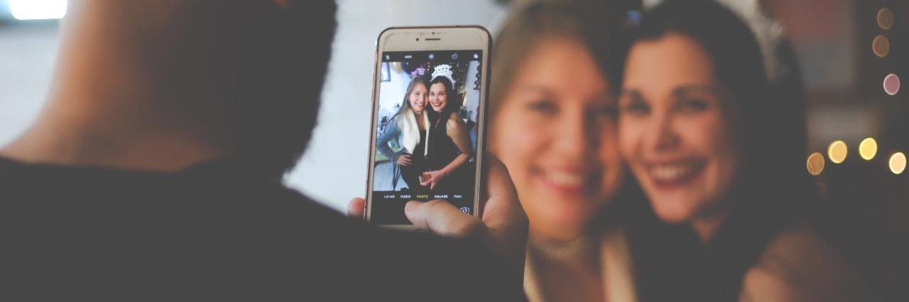 man taking image of two smiling women on smartphone
