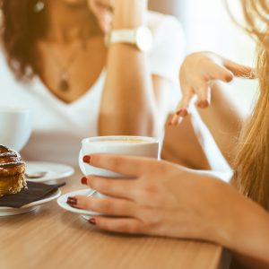 Two friends having coffee and a cupcake. We cannot see their faces but we see from hand positioning they are talking and connecting.