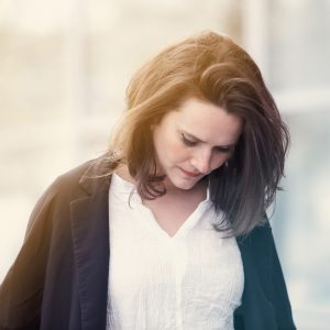 Woman wearing a white shirt and blue sweater looking down, she seems sad