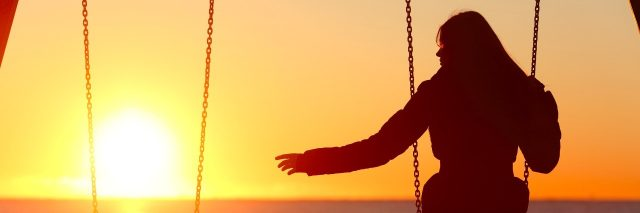 Silhouette of a woman alone on a swing, reaching out to an empty swing