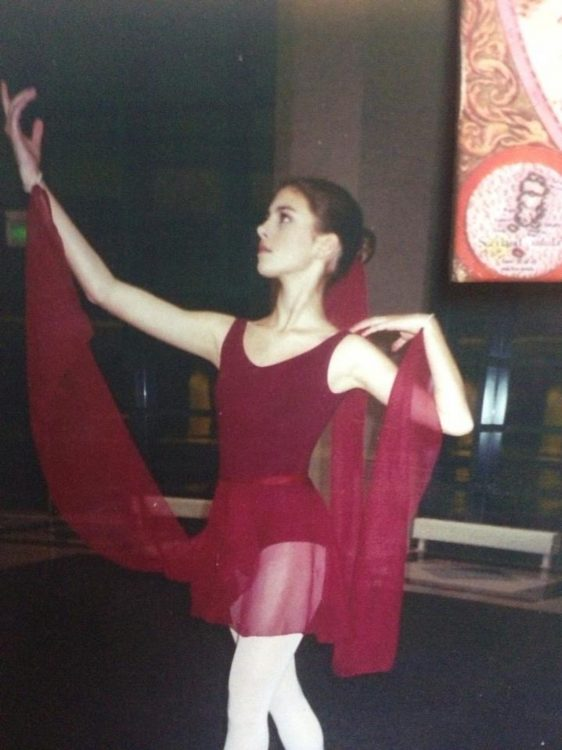 A ballerina in her red costume, dancing.
