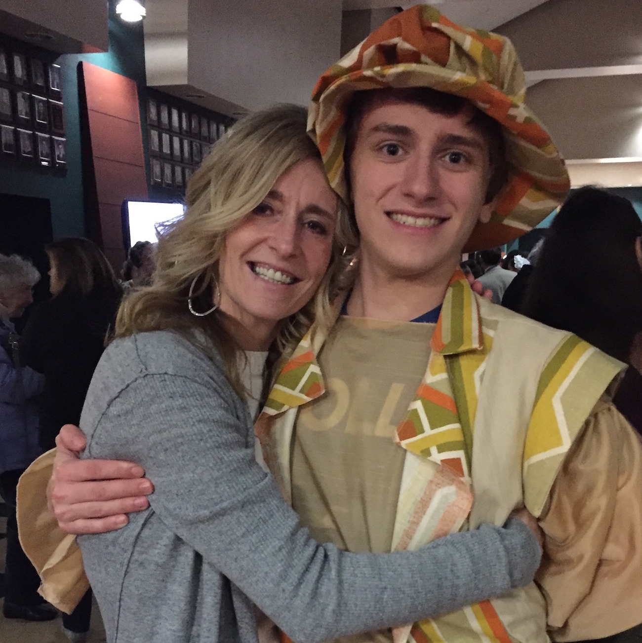 Mother and son hugging, with son in costume from school play