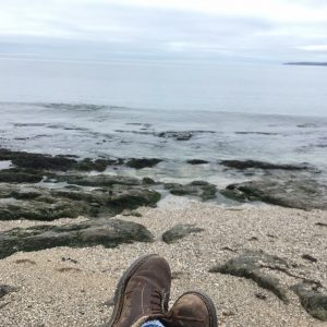 boots on sand overlooking ocean