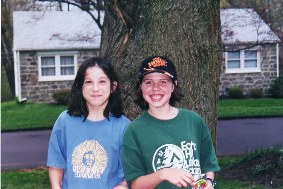 The author and her friend as kids, posting outdoors in front of tree in neighborhood