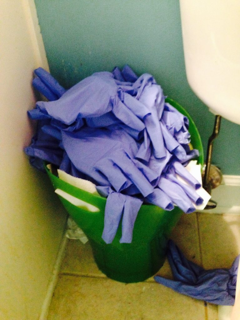 bathroom bin filled with pairs of blue gloves from a single day