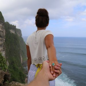 man reaching out holding woman's hand at cliff edge with view of ocean support