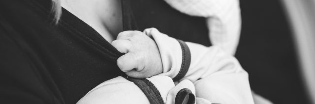 baby holding onto mom's shirt