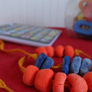 Beads made out red and blue play-doh stringed with a yellow shoe lace