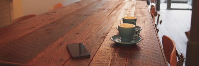 two cups of coffee sitting on coffee shop wooden table beside smartphone