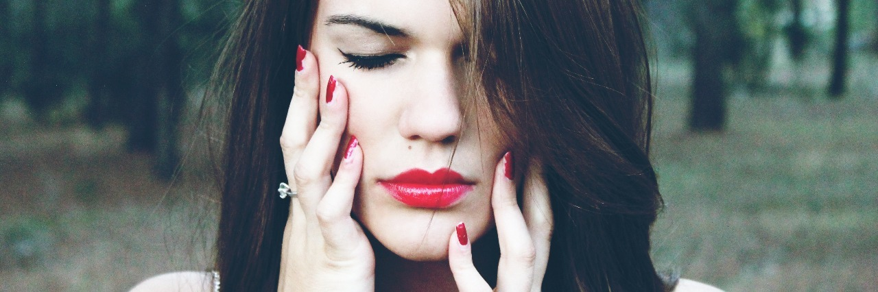 Woman wearing red lipstick with eyes closed and hands on face