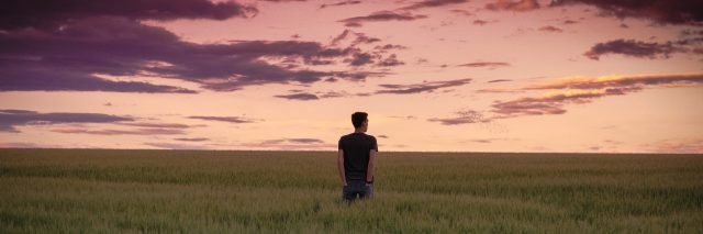 man standing alone in field at sunset