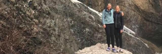 Two friends standing near a waterfall.