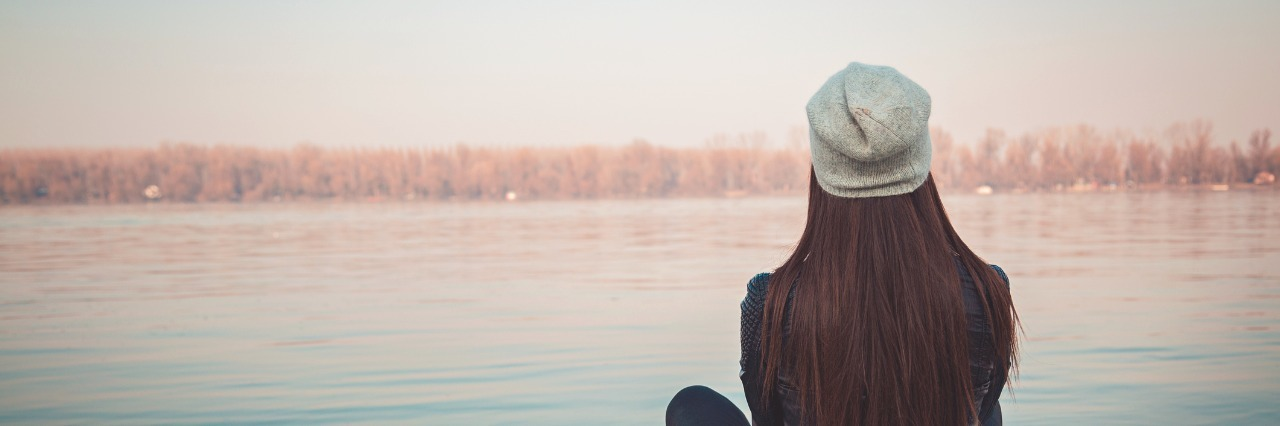 woman sitting on a pier overlooking the water