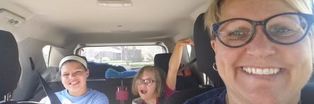 Selfie of autor riding in the car, she has sort blond hair and wears glasses, both her daughters are sitting in the back seat and waving at the camera.