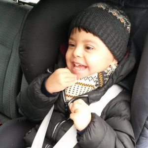 Boy in car seat in car, wearing beanie and laughing