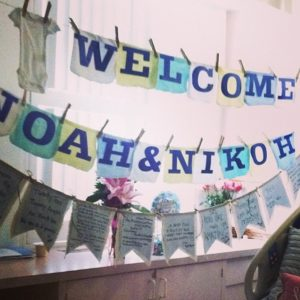 A sign in a hospital room that says [Welcome Noah and Nikoh] with a banner filled with well wishes underneath it
