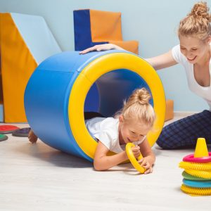 Little girl doing therapy, she is in a roller tunnel reaching for toys while therapist keeps roller steady