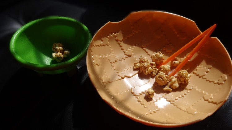 A small green bowl and a large tan bowl, both with popcorn. A pair of orange tongs sits in the tan bowl.