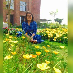 woman sitting in a daisy field