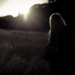 woman watching sunset in field