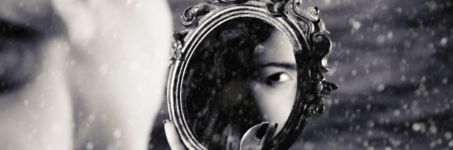 girl looking at reflection in mirror, you can only see her eye