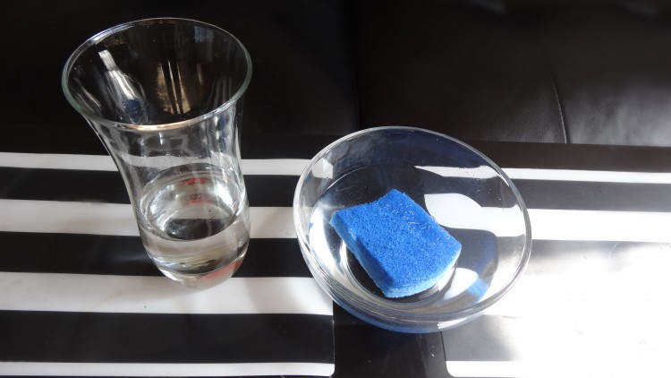 a clear bowl with water and a blue sponge inside, next to it is a clear cup with a small amount of water