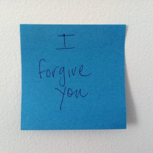 blue post it note with I forgive you written in pen and stuck to wall