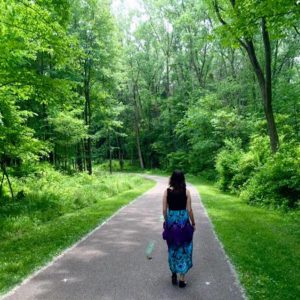 woman walking down a path through a forest