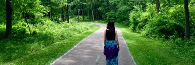 woman walking down a path through a forest