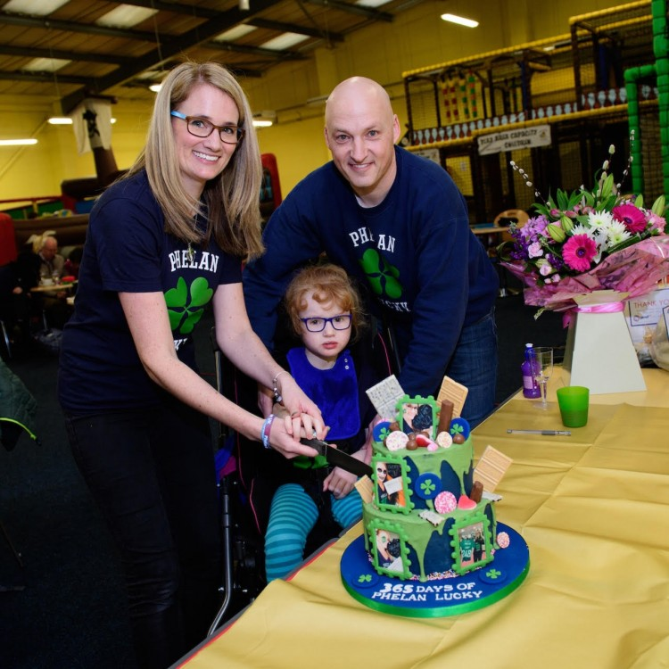 Two parents and their daughter cutting a celebration cake.