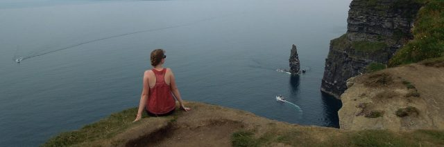 Woman sits on rock, facing water