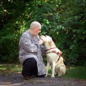Holly and her guide dog in a park, with Holly kneeling next to her guide dog, both of them looking at each other