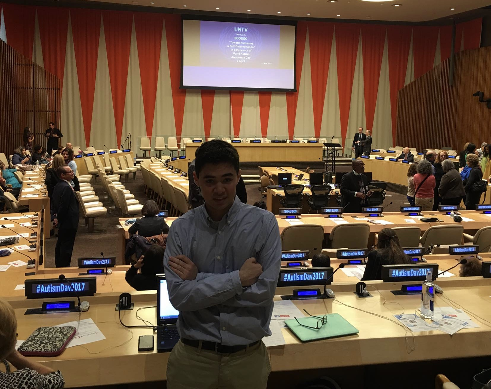 Tom at World Autism Awareness Day 2017 at the United Nations, standing in front of tables with microphones and the stage in the background