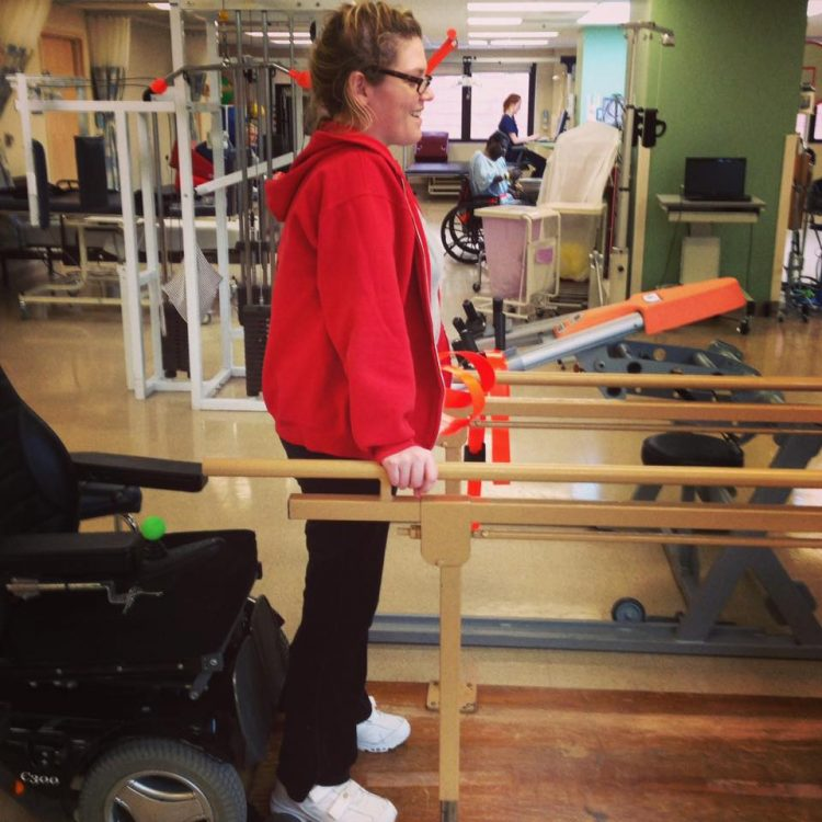 woman standing holding handrails and physical therapy
