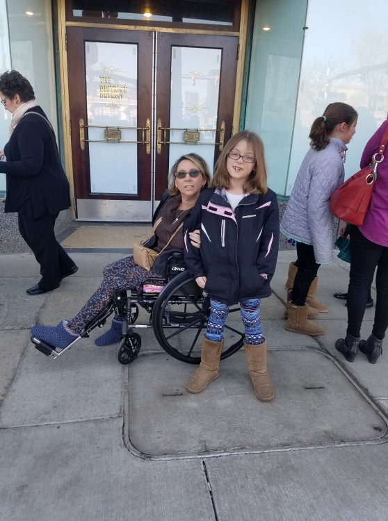 woman in wheelchair next to young girl