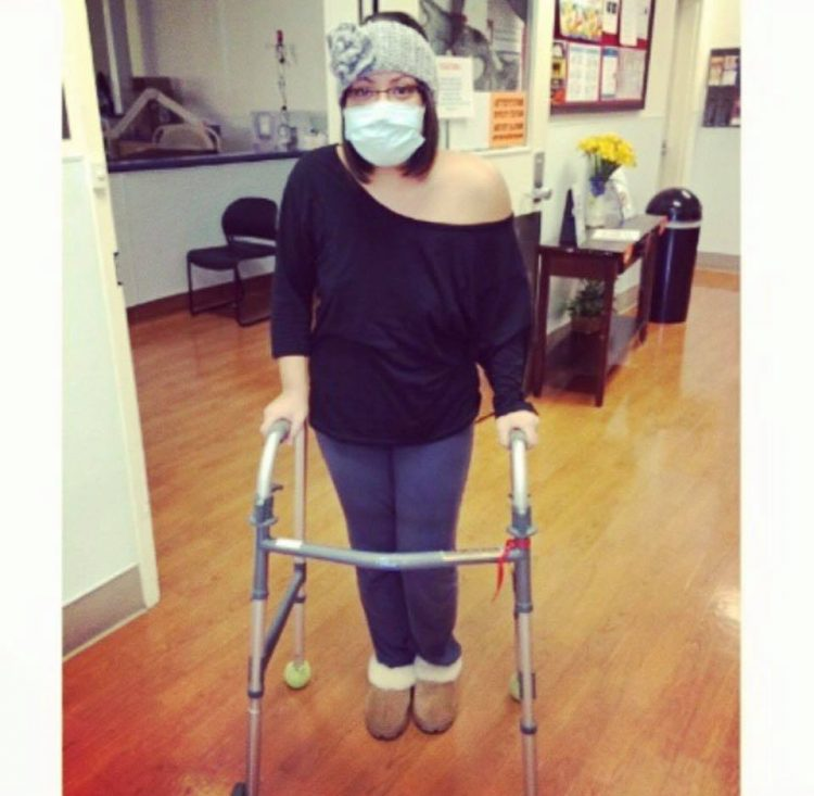 woman standing with walker and wearing surgical mask