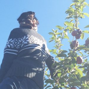 Person in sweater, standing near peach tree